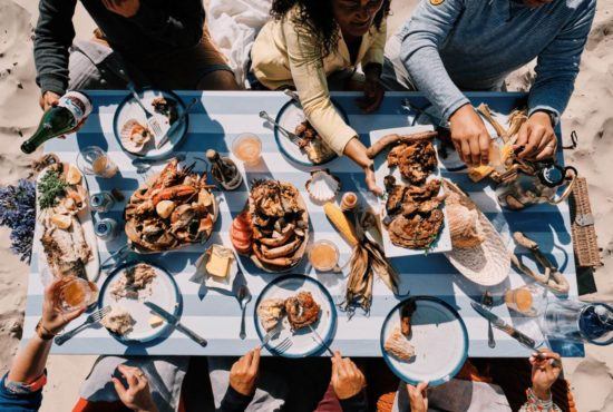 Group of people sharing a beach bbq sat at a table